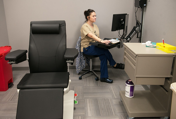 Carrie Bath, lead medical technician, works in the blood draw area of the new Joplin VA Clinic on Monday.<br /> Globe | Roger Nomer