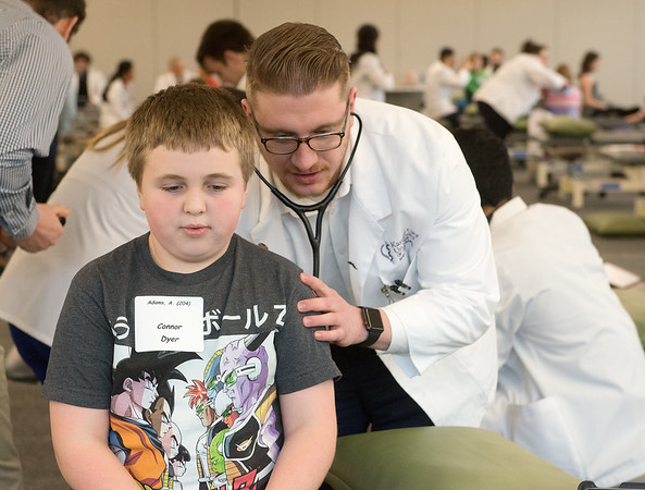 Brandon Tompkins, a second year student from Highland Falls, NY, listens to Connor Dyer's lungs, a fourth grader at West Central Elementary, on Tuesday at Kansas City University of Medicine and Biosciences Joplin.<br /> Globe | Roger Nomer