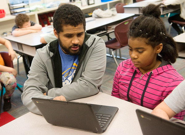 Brock Compton helps Brianna Chasten, a fifth grader at West Central Elementary, with an exercise on a Chromebook on Feb. 1 at the school.<br /> Globe | Roger Nomer