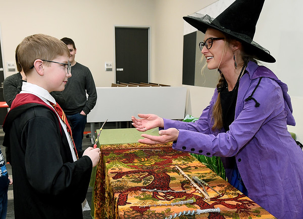 From the left: Nine-year-old Mason Briley gets a wand from Shelley Keezer, assistant at the Joplin Public Library's children's library on Friday during a Harry Potter Celebration Day. Children enjoyed butter beer, snacks, games and more at the popular event.  Globe | Laurie Sisk