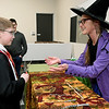 From the left: Nine-year-old Mason Briley gets a wand from Shelley Keezer, assistant at the Joplin Public Library's children's library on Friday during a Harry Potter Celebration Day. Children enjoyed butter beer, snacks, games and more at the popular event. <br /> Globe | Laurie Sisk