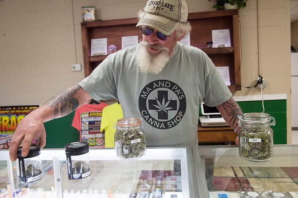 Dean Mitchell talks about products for sale at Ma and Pa's Canna Shop in Grove on Monday.<br /> Globe | Roger Nomer