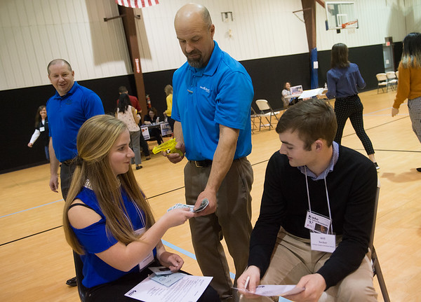 Lydia Rockers, senior at Carthage, and Will Secker, senior at College Heights Christian School, surrender their money as they are robbed by Mark Box during Wednesday's poverty simulation at the Boys and Girls Club of Southwest Missouri.<br /> Globe | Roger Nomer