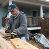 Ted Donaldson, with Compass Quest, works with lumber during a repair workday at a veteran's house in Joplin on Friday.<br /> Globe | Roger Nomer