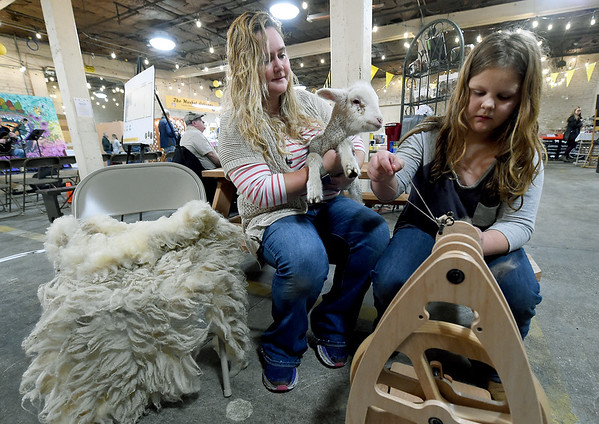 """Ten-year-old McKensey Teel deomonstrates her spinning skills as her mother, Lindsey Teel and pet lamb """"Sprout"""" observe on Saturday at the Empire Market. McKensey runs her own booth, """"Sweet Springs,'  at the market and features spun wool as well as completed purses, scarves, hats and more.<br /> Globe 