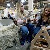 "Ten-year-old McKensey Teel deomonstrates her spinning skills as her mother, Lindsey Teel and pet lamb ""Sprout"" observe on Saturday at the Empire Market. McKensey runs her own booth, ""Sweet Springs,'  at the market and features spun wool as well as completed purses, scarves, hats and more.<br /> Globe 
