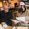 Scott Hettinger, president of Charlie 22 Outdoors, left, and Justin Maggard, board member, talk about veteran's applications to the program over lunch at Cantina Bravo on Friday, Feb. 15.<br /> Globe | Roger Nomer