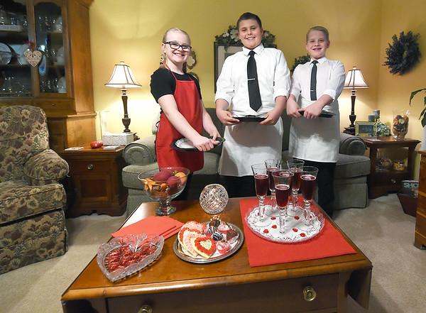 From the left: Kady Hunt, 10, Shaun Hunt, 12 and Chase Hunt, 12, stand poised to serve their parents before their arrival for an annual Valentines dinner on Saturday at their grandmother, Tammy Hunt's home. Kay and Chase are siblings and Shaun is their cousin.<br /> Globe | Laurie Sisk