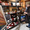 Beth Sellers looks over the selection of pieces to be raffled off during the Local Color Art Gallery Open House at the gallery on Friday. Proceeds from the raffle will benefit the Breast Cancer Foundation of the Ozarks.<br /> Globe | Laurie Sisk