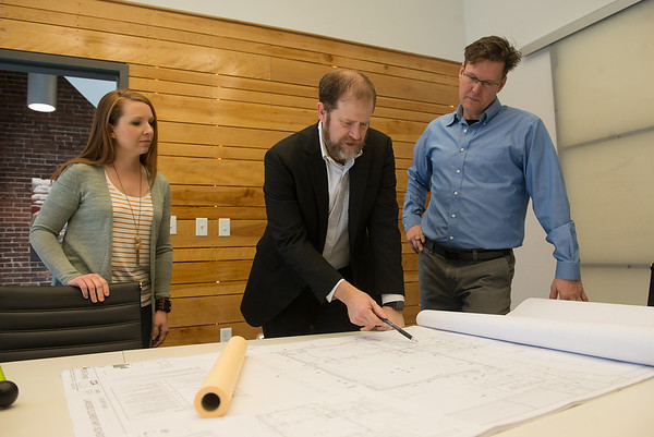 (from left) Christina Williams, project designer, Chad Greer, principal, and Michael Wischmeyer, principal, look over plans for an elementary school at Corner Greer Architects on Wednesday.<br /> Globe   Roger Nomer