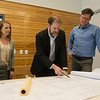 (from left) Christina Williams, project designer, Chad Greer, principal, and Michael Wischmeyer, principal, look over plans for an elementary school at Corner Greer Architects on Wednesday.<br /> Globe | Roger Nomer