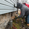 Ted Donaldson, with Compass Quest, helps transport wood underneath a veteran's house in Joplin on Friday.<br /> Globe | Roger Nomer