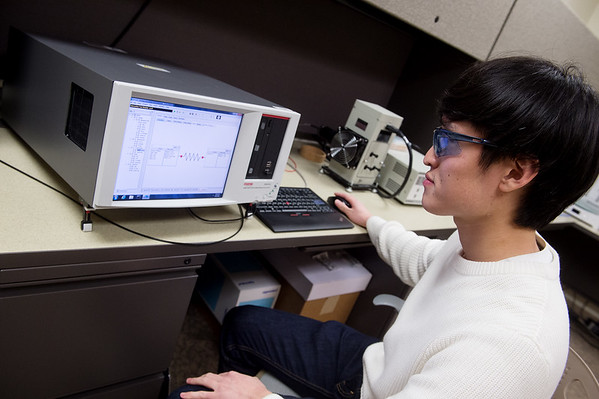 Jong Hyun Choi, graduate student at Pittsburg State University, demonstrates measuring the properties of a battery on Tuesday at PSU's Kansas Polymer Research Center in Pittsburg.<br /> Globe | Roger Nomer