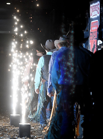 Cowboys parade past a string of pyrotechnics during introductions for the LJ Jenkins Bull Riding Tour Finals on Saturday night at Memorial Hall.<br /> Globe   Laurie Sisk
