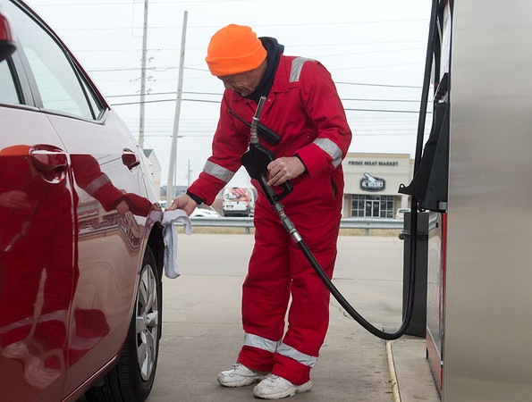 Paul Schaefer, owner of Doc's Stop, wipes down a customer's car after a fill up as part of the station's full service on Monday.<br /> Globe   Roger Nomer