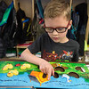 Amos Little, kindergartener at Pleasant Valley Elementary, reads from a book on Friday at the school. Little was one of the students identified as needing glasses by a recent screening.<br /> Globe | Roger Nomer