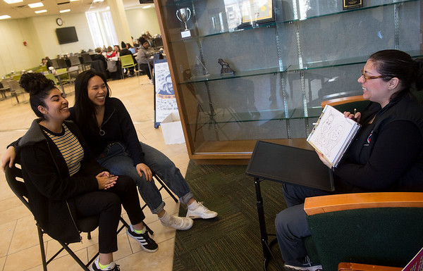 BeeJay Hawn, with Speed Sketchers KC, shows Indira Madrigal (left) and Mary Pham, both freshmen at Missouri Southern State University, her speed caricature of them on Friday at MSSU. The MSSU Campus Activities Board presented the event. <br /> Globe | Roger Nomer