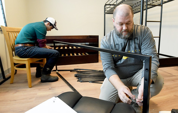 From the left: Royce Ingram, a volunteer fron the Young Professionals Netqork and Matt Ingle, director of the Washington Family Hope Center, piece together a trundle bed in one of the apartments at the center on Wednesday. Once open, the center will feature six apartments for single mothers with up to four kids each. The project is part of Watered Gardens.<br /> Globe | Laurie SIsk