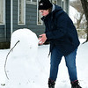 Sixteen-year-old Ahava Kuhler braves the cold as she fashions a large snowman on North Sergeant Avenue on Wednesday.<br /> Globe | Laurie Sisk