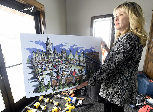 Becky Andrews holds an artist's rendering of the Gadarian Event Center's rooftop venue that is currently under construction on the Carthage square.<br /> Globe | Laurie SIsk