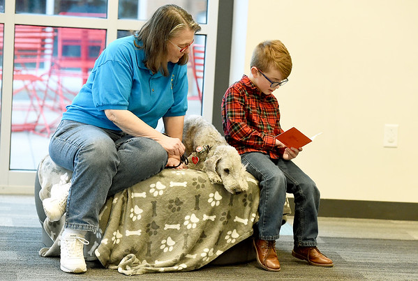 """Six-year-old Rhett McConnell practices his reading skills as he reads to """"Ricky,"""" a Bedlington terrier and Ricky's owner Debbie Miller during Dog Day Afternoon on Tuesday at the Joplin Public Library.  MCConnell has been practicing his reading skills in hopes of reading to a pup during the popular program.<br /> Globe 