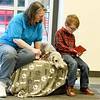 "Six-year-old Rhett McConnell practices his reading skills as he reads to ""Ricky,"" a Bedlington terrier and Ricky's owner Debbie Miller during Dog Day Afternoon on Tuesday at the Joplin Public Library.  MCConnell has been practicing his reading skills in hopes of reading to a pup during the popular program.<br /> Globe 