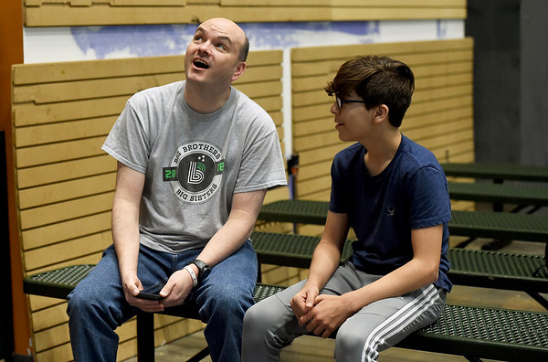 From the left Big Brother Mike Brown looks at the climbing wall that Braiden Windle, 14, scaled for the first timeat Victory Ministry and Sports Complex on Saturday.<br /> Globe | Laurie Sisk