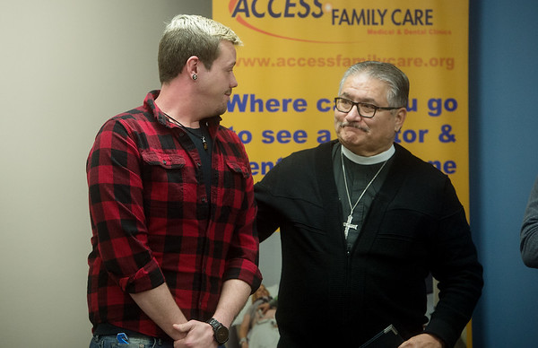 Rev. Frank Sierra (left), of St. Philip's Episcopal Church, thanks Patrick Burrows for talking about his experience with a lack of health care on Thursday at Access Family Care. Globe | Roger Nomer