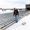 Brandon Calliote stands on the supports of what will be a cedar deck for the Gadarian Event Center's rooftop venue that is currently under construction on the Carthage square.<br /> Globe | Laurie SIsk
