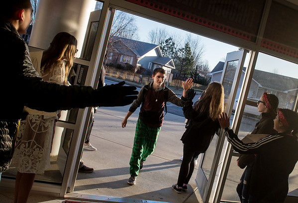 Elijah Corben, sophomore at Carl Junction High School, gets high fives as he arrives at school from the Kids Recognizing Everyone's Worth group on Friday.<br /> Globe | Roger Nomer