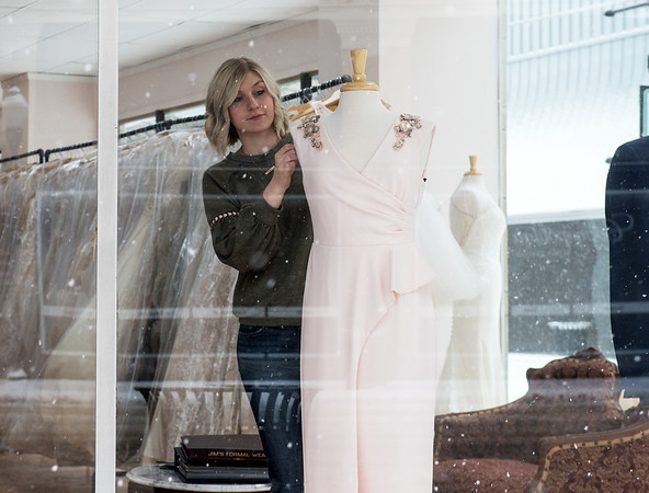 As snow falls in downtown Joplin, Kaylee Meyer arranges a window dispay at Rosa Bella Bridal and Formal Boutique on Wednesday.<br /> Globe | Roger Nomer