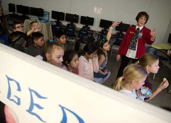 Linda Gregersen, reading specialist at Fairview Elementary in Carthage, talks about the city of Barcelona during a trip on Tiger Airlines on Friday.<br /> Globe | Roger Nomer