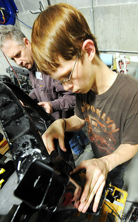 Globe/T. Rob Brown<br /> Drew Holle, a Joplin High School junior, works on repairs to the front end of a vehicle as instructor Douglas England looks on Tuesday afternoon, Jan. 31, 2012, in the auto collision repair class at Franklin Tech.