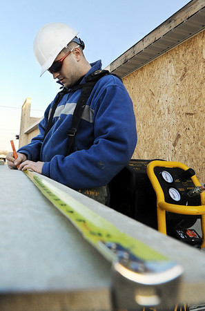 Globe/T. Rob Brown<br /> Carpenter Brandon Rickard with J.L. Construction of Ozark, measures a board Monday afternoon, Jan. 9, 2012, during the rebuilding of Pizza Hut on Main Street.