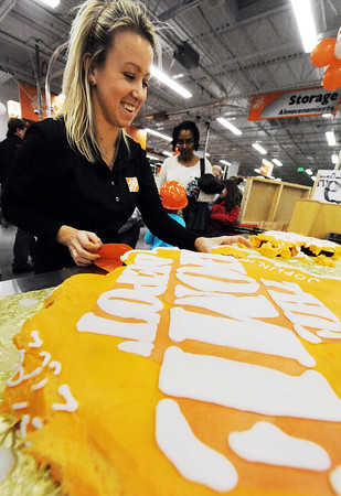 Globe/T. Rob Brown<br /> Leigh Wildman, The Home Depot event planning employee from corporate in Atlanta, hands out cupcakes during the grand re-opening event Wednesday evening, Jan. 11, 2012, for The Home Depot on Range Line Road in Joplin.