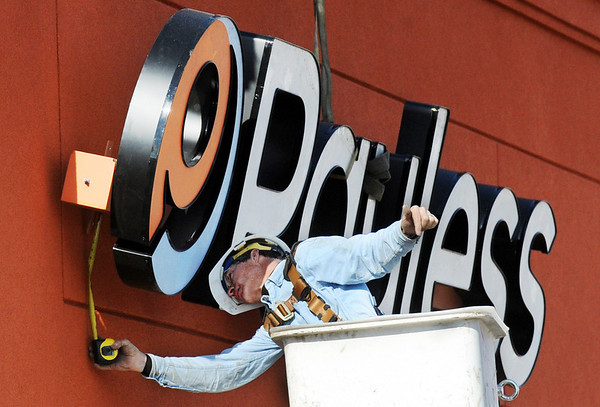 Globe/T. Rob Brown<br /> Sonny Garman, owner of All Season Signs, of Joplin, directs a crane operator as he installs the Payless Shoesource sign to the front of the store Thursday afternoon, Jan. 19, 2012, on Range Line Road in Joplin. The former building at this location was destroyed during the May 22, 2011, tornado.