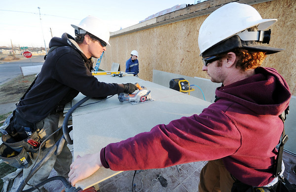 Globe/T. Rob Brown<br /> Jacob Lemaster (left), owner of J.L. Construction of Ozark, cuts a board as carpenter Justin Rickard holds the board steady Monday afternoon, Jan. 9, 2012, during the rebuilding of Pizza Hut on Main Street.