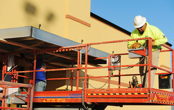 Globe/T. Rob Brown<br /> Scott Whitman, owner of Whitman Contractors LLC, a subcontractor with Larry Snyder & Co., operates a lift as he and his employee Joe Snodgrass install an awning Monday afternoon, Jan. 9, 2012, during the rebuilding of Backyard Burgers on Range Line Road.