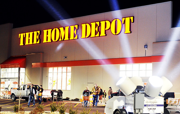 Globe/T. Rob Brown<br /> Customers walk out under spotlights at The Home Depot on Range Line Road in Joplin after making their purchases during the store's grand re-opening Wednesday night, Jan. 11, 2012.