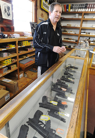 Globe/T. Rob Brown<br /> Steve, owner of Steve's Trading Post on South Main Street, speaks to a customer about handgun sales Tuesday afternoon, Jan. 8, 2013. He said he is worried about some talk of trying to do away with all guns that have magazines, which would affect even the Glock, a widely sold pistol.