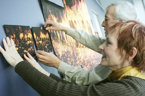 """Globe/Roger Nomer<br /> Cleo Copeland and Tom Brown hang a piece by Regina V. Benson called """"Wildfire"""" at the Spiva Art Gallery on Thursday."""