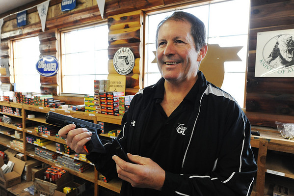 Globe/T. Rob Brown<br /> Steve, owner of Steve's Trading Post on South Main Street, holds a pistol that utilizes a magazine Tuesday afternoon, Jan. 8, 2013. He said he is worried about some talk of trying to do away with all guns that have magazines, which would affect even the Glock, a widely sold gun.