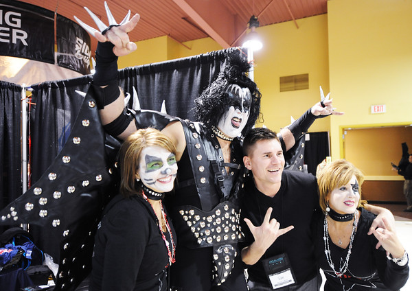 Globe/T. Rob Brown<br /> Dr. Dan Young, dentist with Young Family & Cosmetic Dentistry, center, portrays rock band KISS lead singer Gene Simmons, with fellow bandmates Lori Young, left, and Melody Morgan, office manager, right, as they pose for a rockin' photo with George Hoffman, of Pearson Kelly Office Products and a standup comedian from Springfield, Tuesday afternoon, Jan. 22, 2013, during the Joplin Business Expo at the Holiday Inn Convention Center.