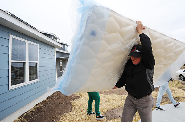 Globe/T. Rob Brown<br /> Octavio Rodriguez carries in a new mattress, which was part of a delivery donated by Convoy of Hope and St. Vincent de Paul of St. Mary's Catholic Church Wednesday morning, Jan. 30, 2013, at the new Rodriguez home in the 2300 block of South Kentucky Avenue. The Rodriguez family lost their home during the May 2011 tornado.