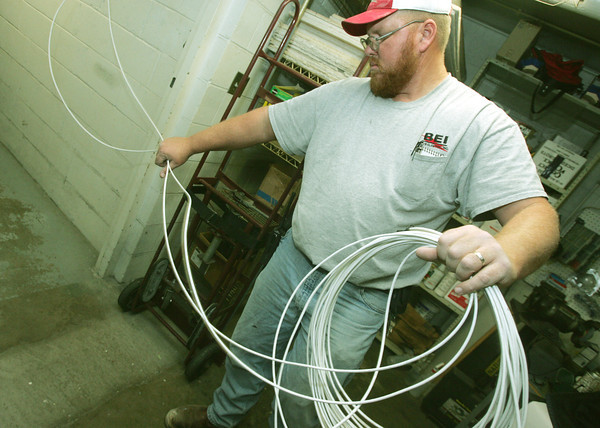 Globe/Roger Nomer<br /> Tom Demster, with Bill's Electric, strings wire for the new security system at the Jasper County Jail on Wednesday.