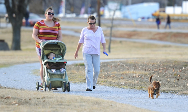 Globe/T. Rob Brown<br /> Taking advantage of Friday's warmer temperatures, (from left) Sarah Henry and her 11-month-old son Peyton Gustafson walk with Gustafson's grandmother, Marcia Sherwood and her dog Murphy at Campbell Park in Joplin.