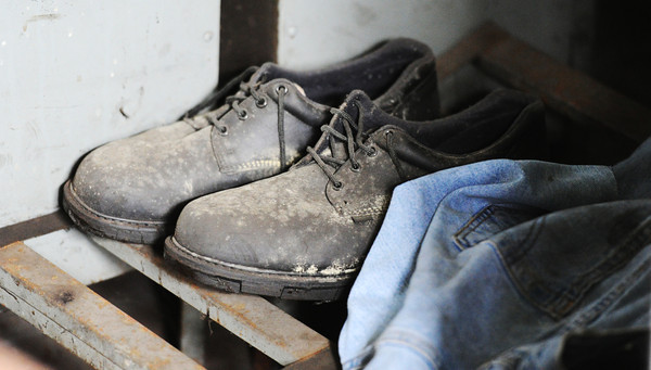 Globe/T. Rob Brown<br /> A leftover pair of work shoes and work pants sit where they have remained for more than a decade in the locker room of the Machine Division of the former McNally Pittsburg Manufacturing Corp. facility in Pittsburg, Kan., Thursday morning, Jan. 24, 2013. The building was recently purchased by CDL Electric Company Inc.