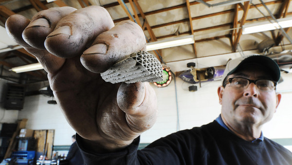 Globe/T. Rob Brown<br /> Mike Fogerson, co-owner and operator of Comer's Muffler Center, holds up a piece of metal from inside a catalytic converter Wednesday morning, Jan. 23, 2013, at the Joplin business.