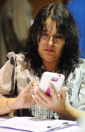 Globe/T. Rob Brown<br /> Job seeker Kimberly Sampson, of rural Neosho, checks her phone for her references' contact information while filling out a job application at a table during the 2013 Job Fair Tuesday afternoon, Jan. 29, in a crowded Holiday Inn Convention Center.