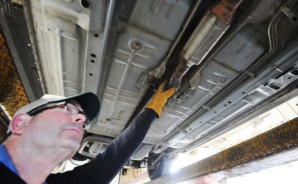 Globe/T. Rob Brown<br /> Mike Fogerson, co-owner and operator of Comer's Muffler Center, takes a look at the catalytic converter on a customer's car Wednesday morning, Jan. 23, 2013, at the Joplin business.